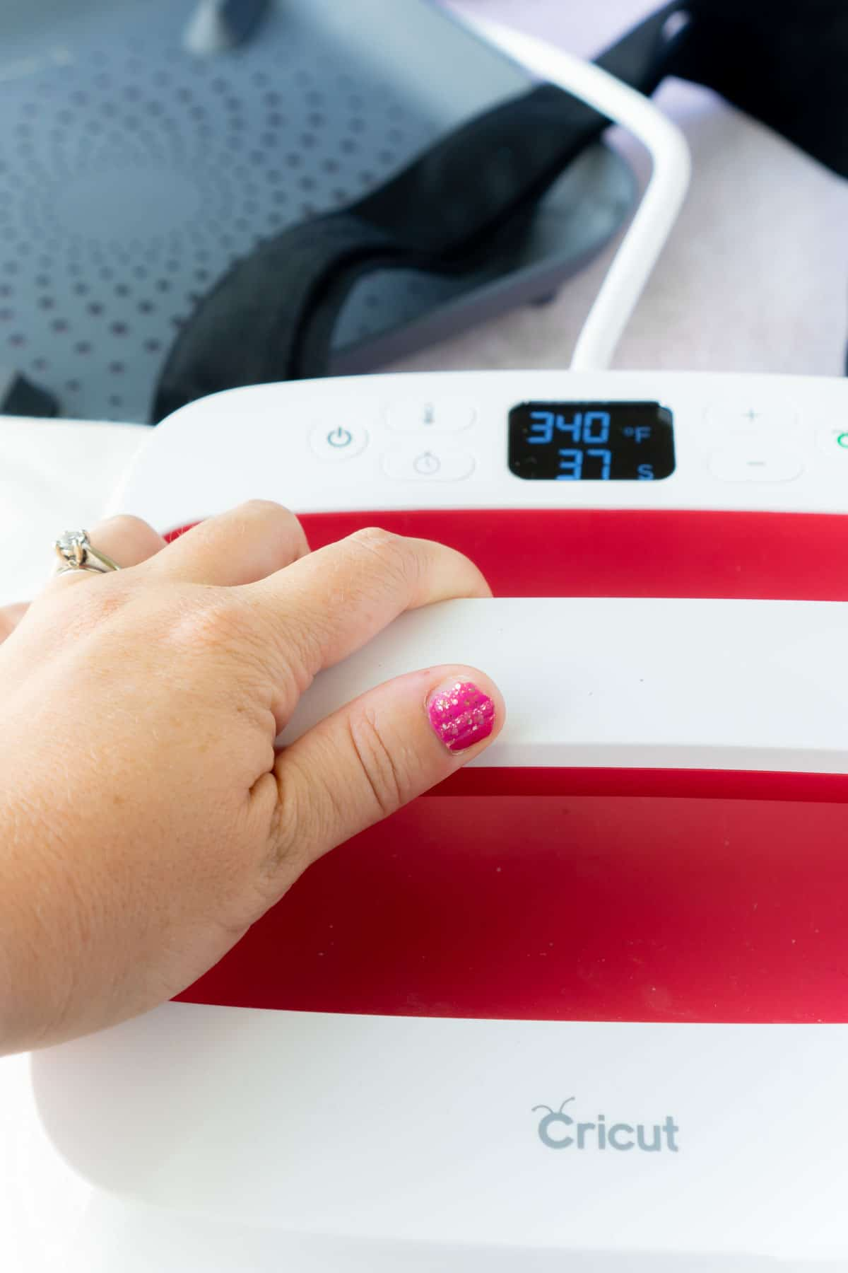 Woman's hand pressing down on a pink Cricut EasyPress