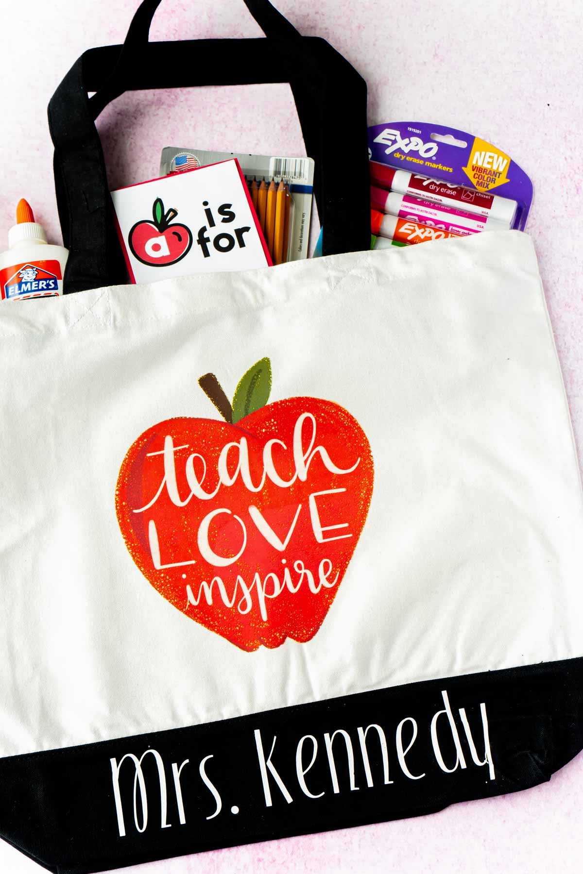 A tote bag with an apple and school supplies sticking out