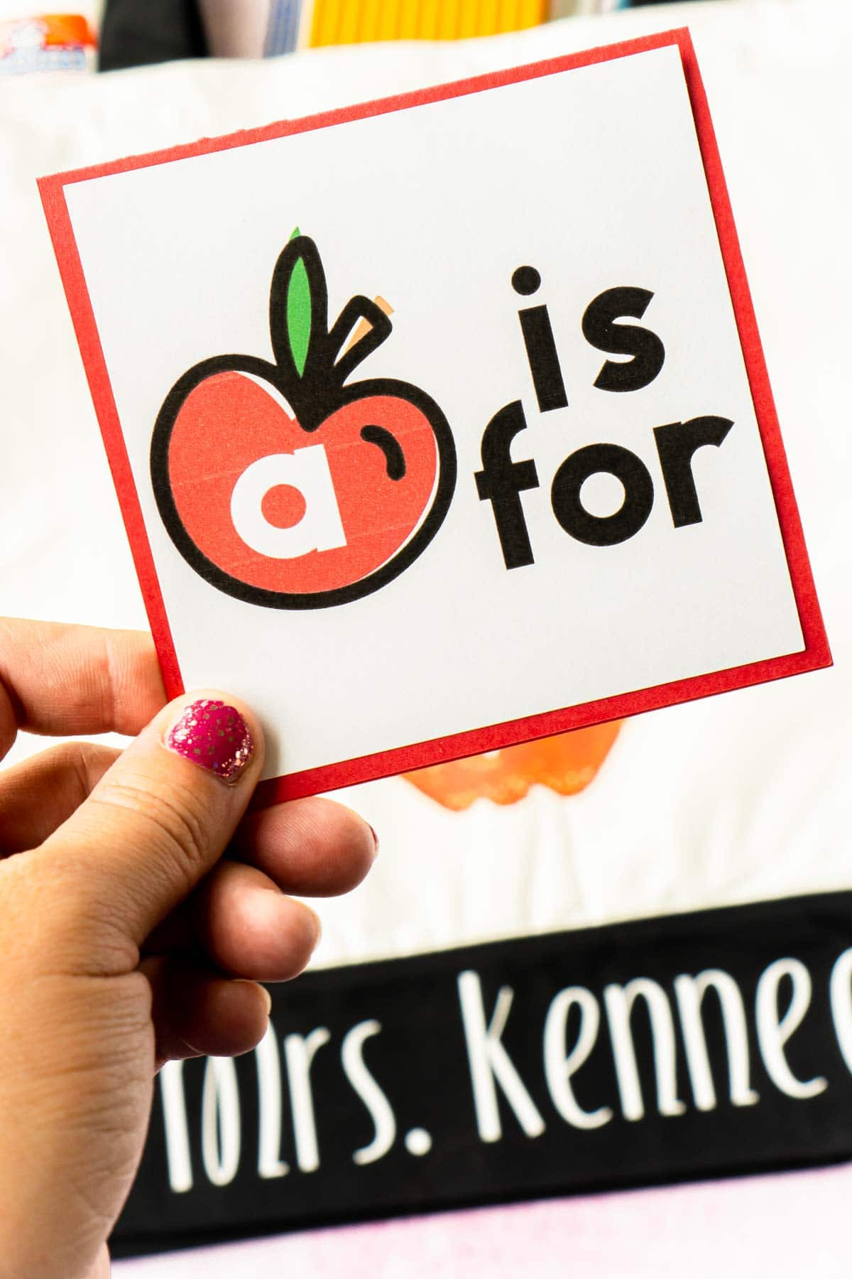 A woman's hand holding an A is for card over a tote bag