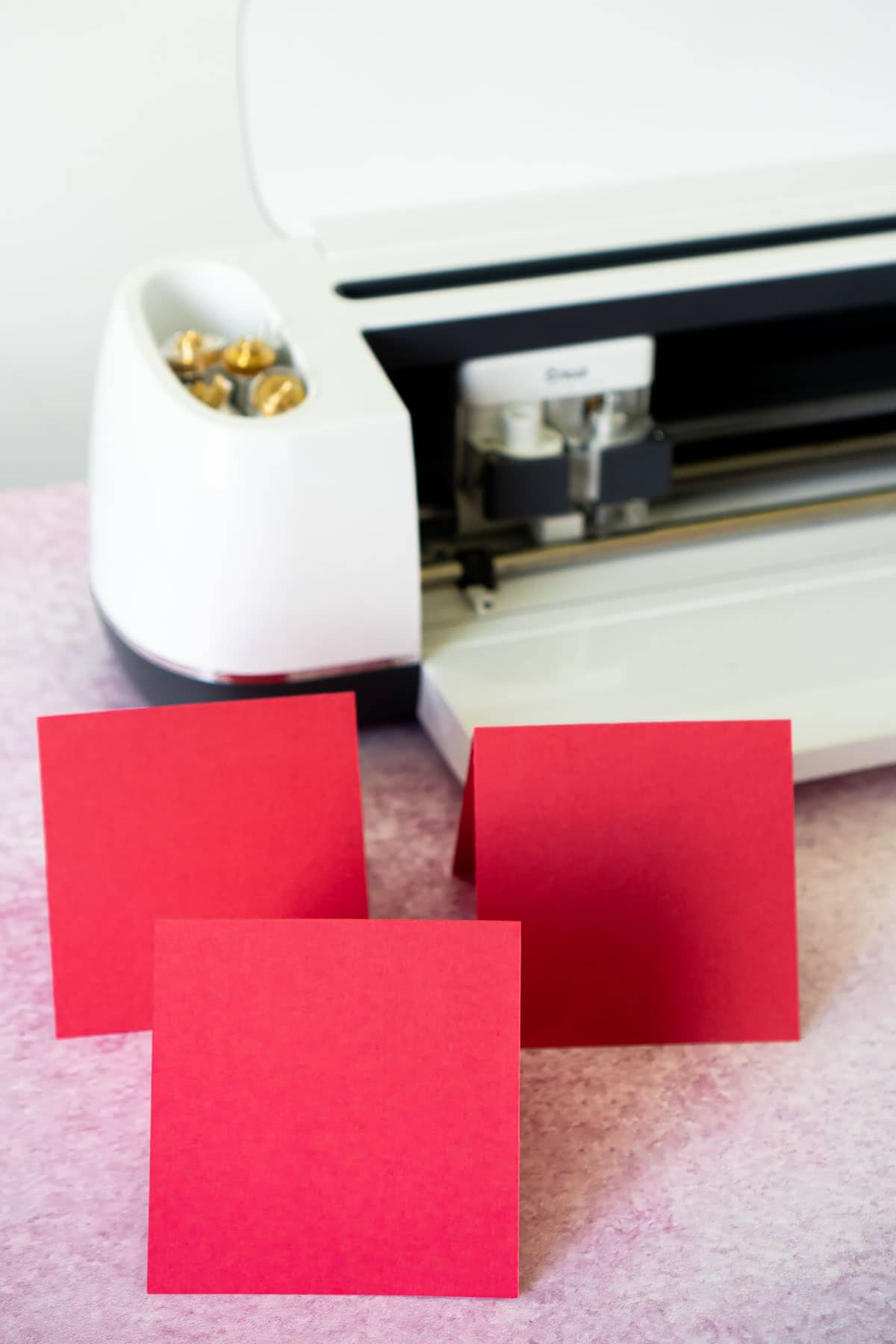 Three pieces of red cardstock cut and folded into front of a Cricut Maker