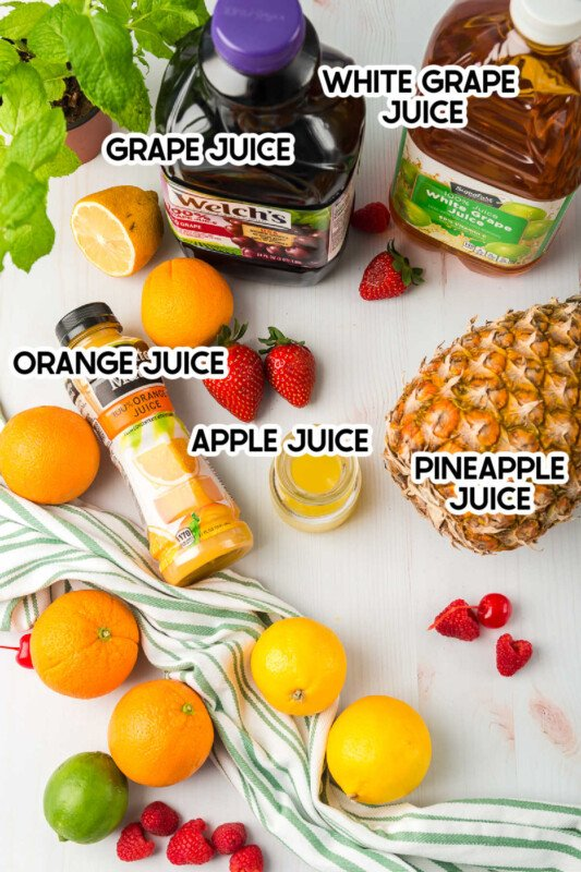 Tons of fruit and bottles of juice on a white background