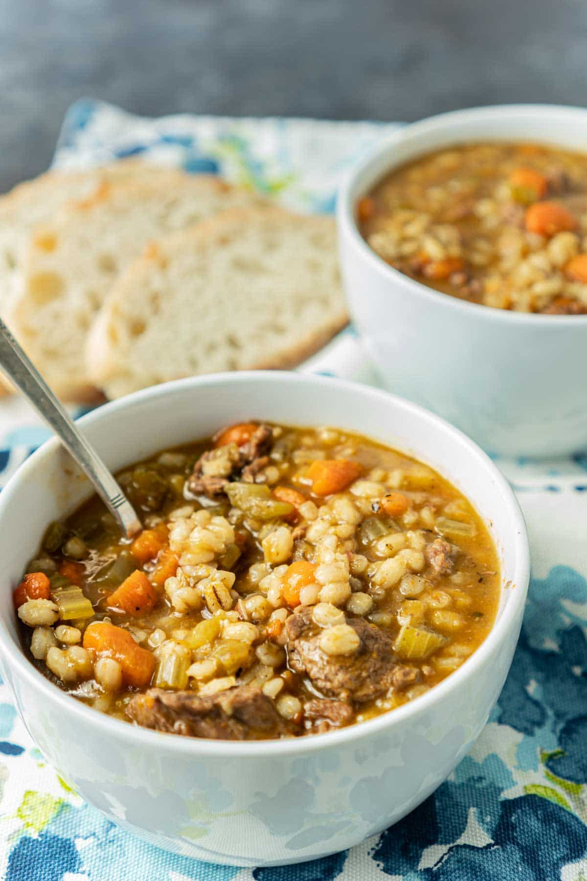 Two white bowls full of beef barley soup with bread in the background