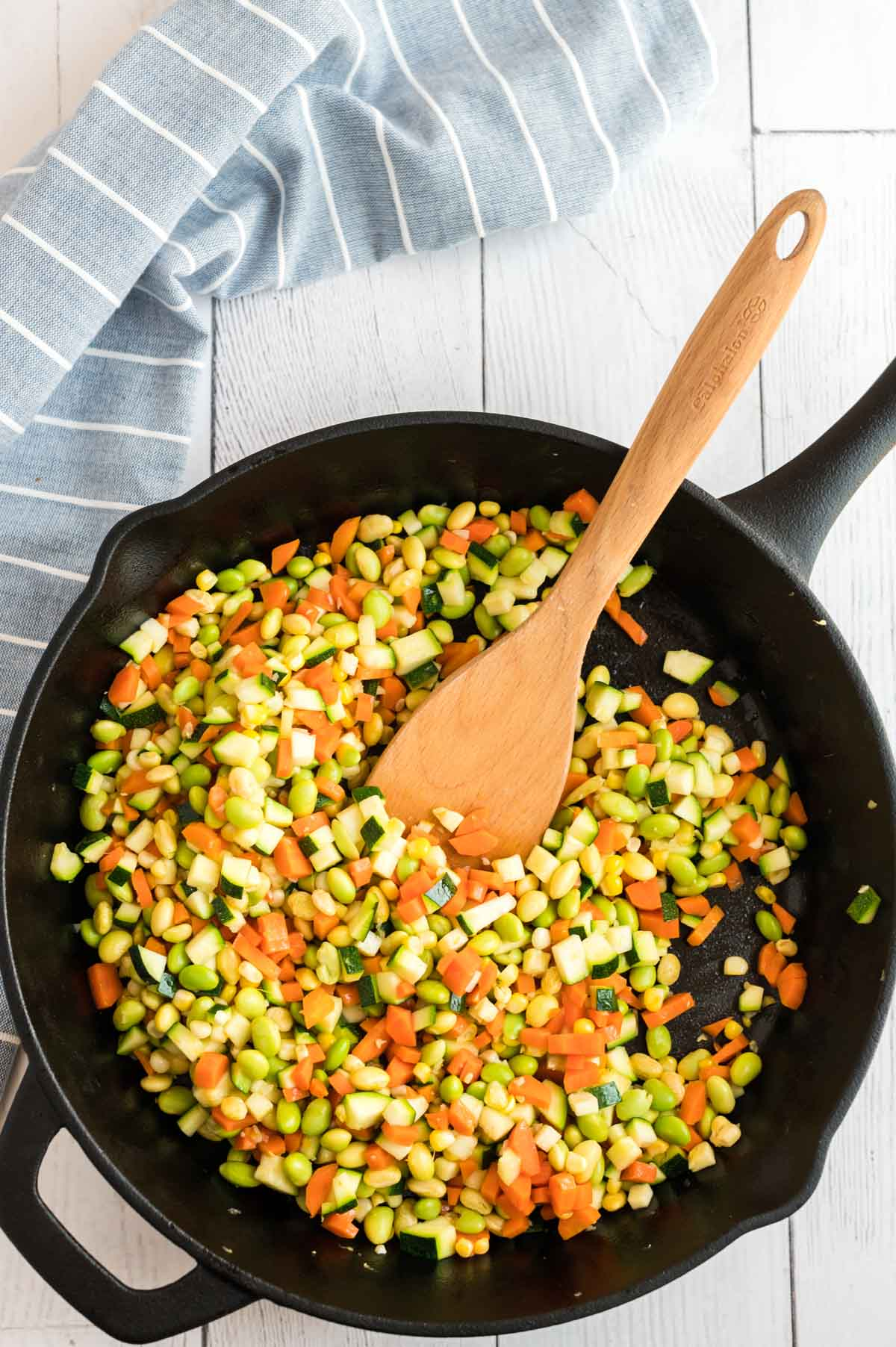 Chopped carrots, zucchini, corn, and garlic in a cast iron pan