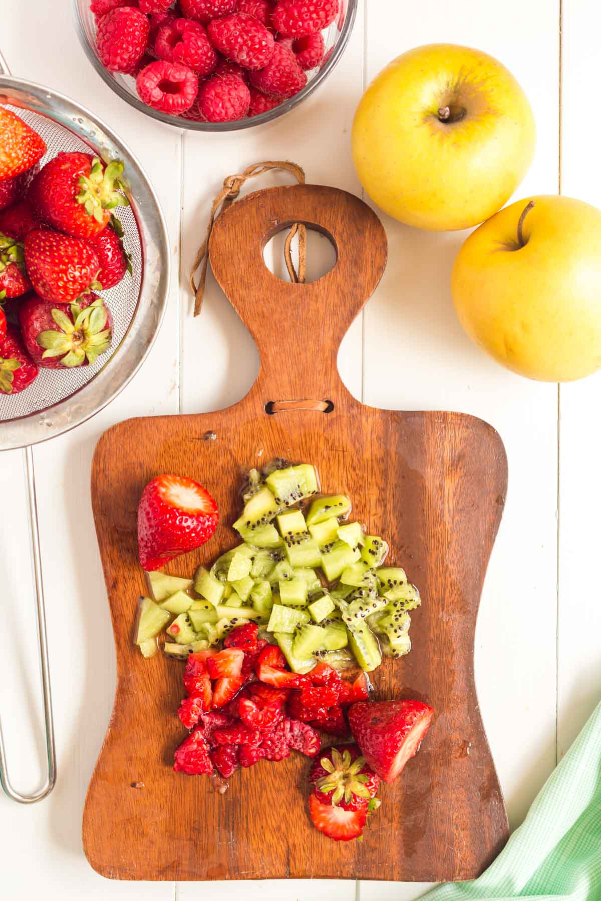 Cutting board with diced strawberries and kiwi with fruit around on the table