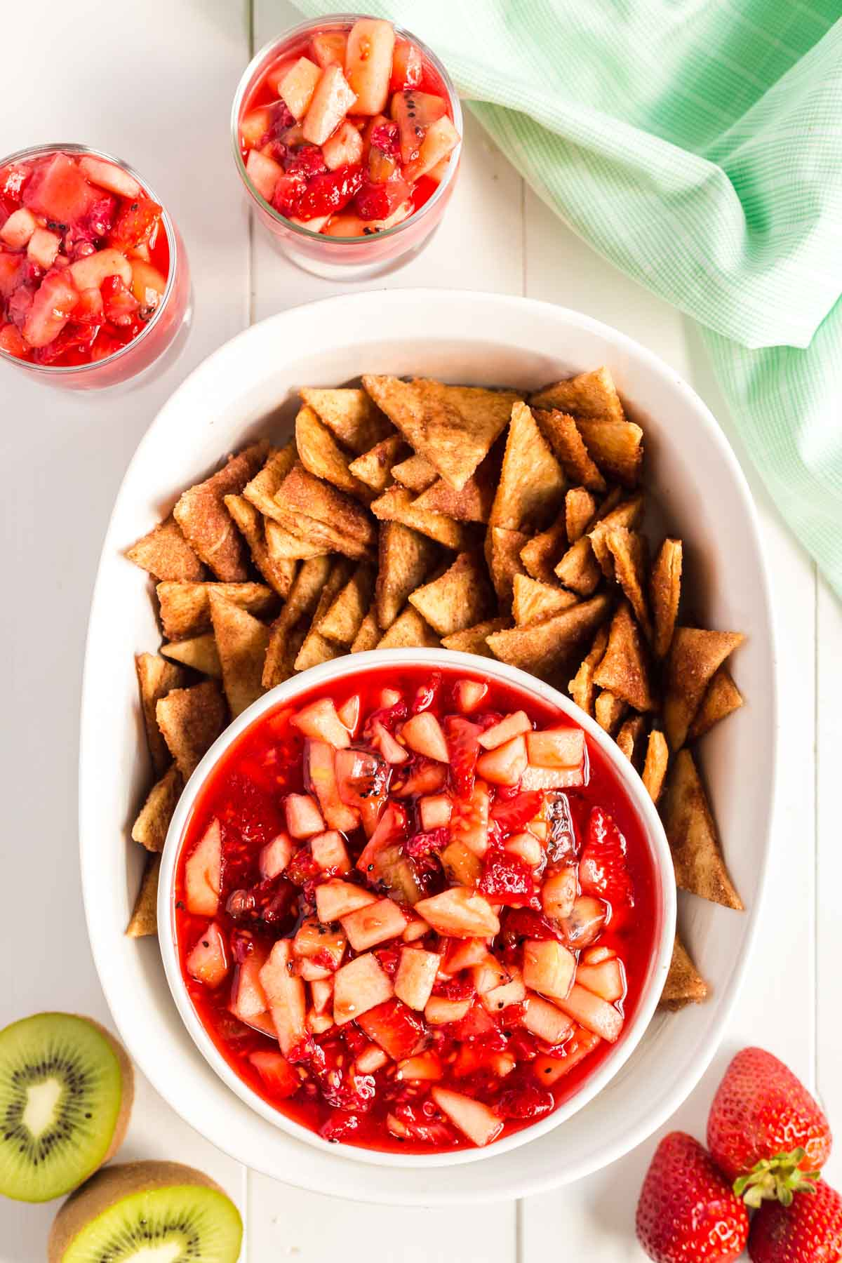 White bowl full of homemade cinnamon chips with a white bowl of fruit salsa