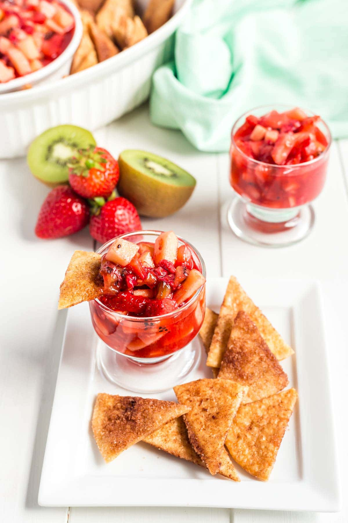 A small glass of fruit salsa on a plate with cinnamon chips and fruit salsa in the background