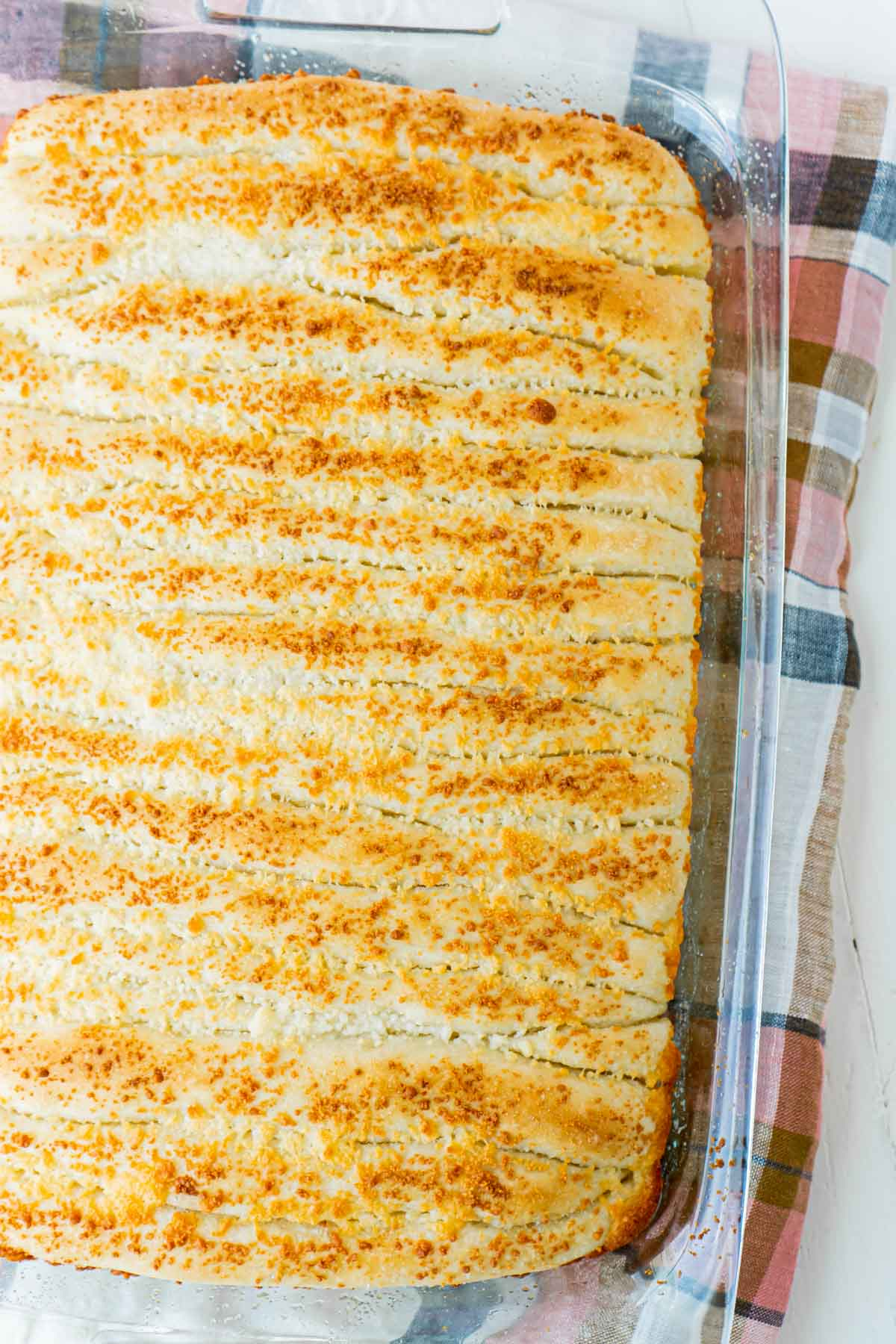 Baked garlic breadsticks in a glass baking dish on a pink and blue napkin