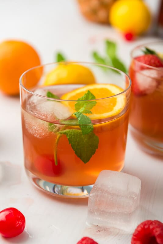 A glass of homemade fruit punch with oranges and ice cubes