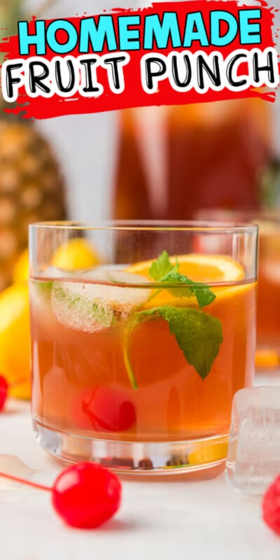 Glass of fruit punch in front of a pitcher of fruit punch with fruit all around with text for Pinterest