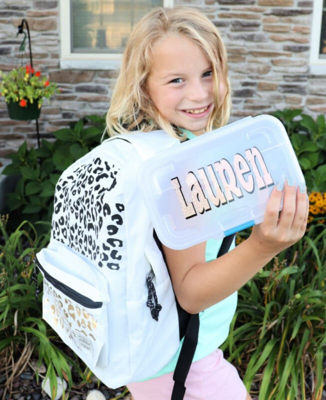 Young girl holding a pencil case that says Lauren and wearing a leopard print backpack