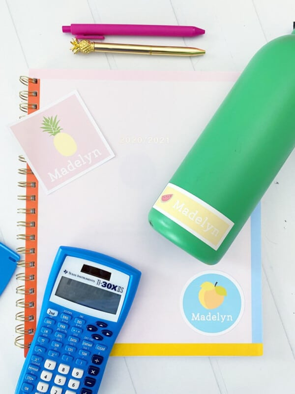 A notebook with school supplies around and personalized stickers for labeling