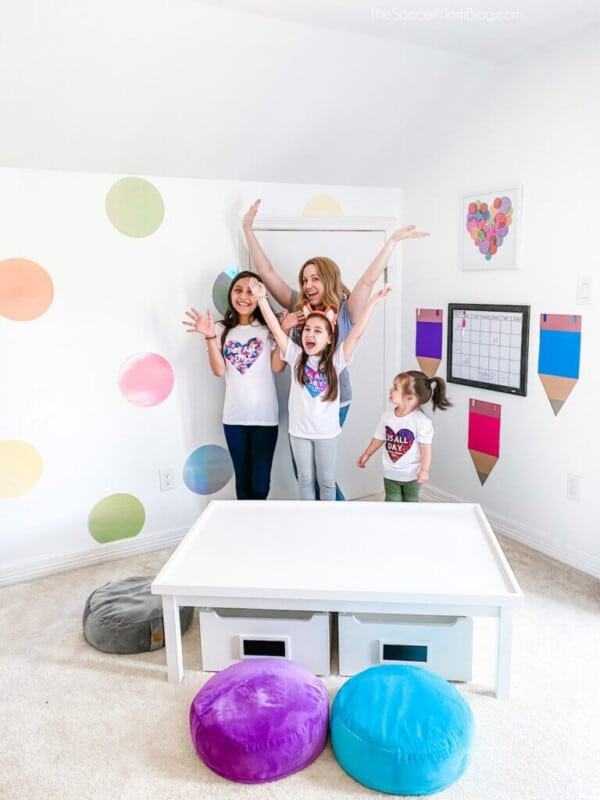 Girls in a room with polka dots on the wall and bean bag chairs and a white table