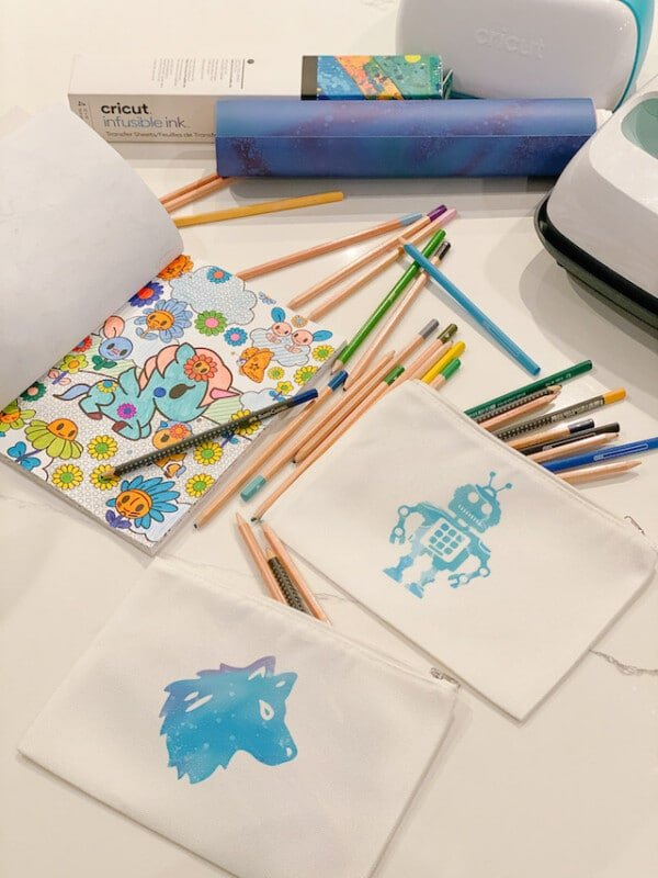 White school supply bags with a wolf and robot on them with pencils strewn about