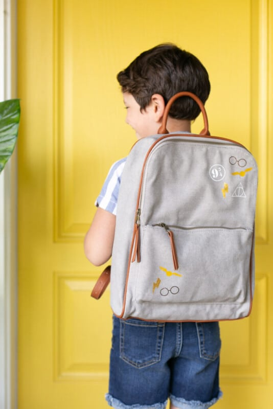 Boy standing in front of a yellow door with a Harry Potter backpack on