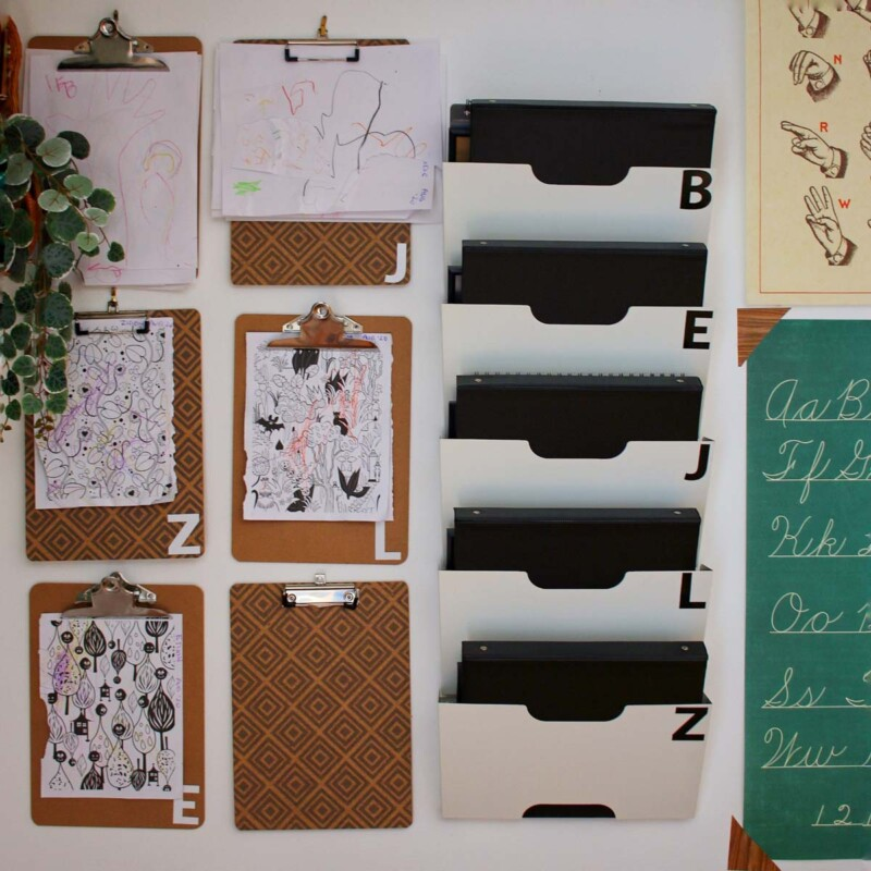 Clipboards and file folders on the wall with colorful sheets of paper