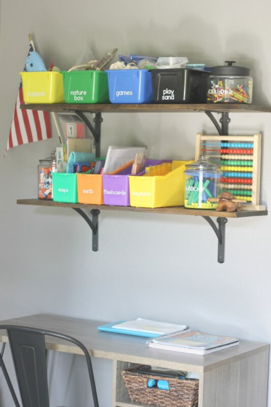 A shelf with colorful storage buckets, labels, and personalize school supplies