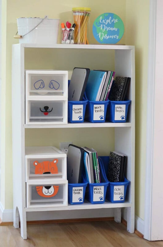Storage containers on a white shelf with school supplies inside