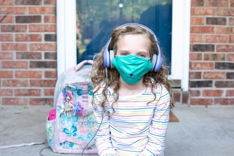 A young girl wearing a personalized mask and holding a backpack