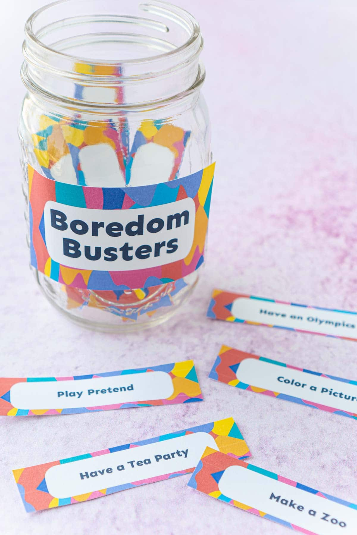 A mason jar with a boredom buster label and a bunch of boredom busters on the table in front of it