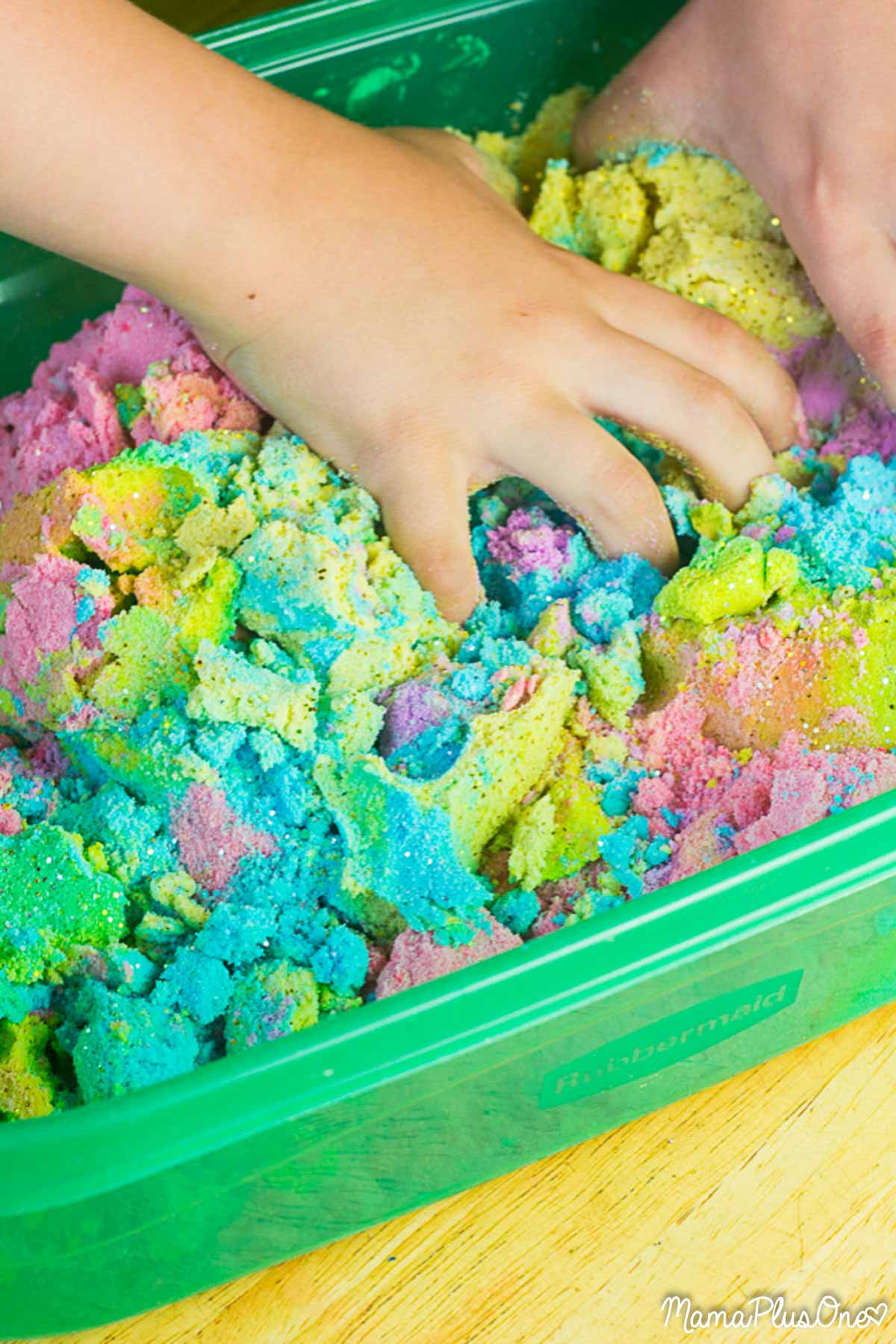 Kid playing in rainbow colored kinetic sand
