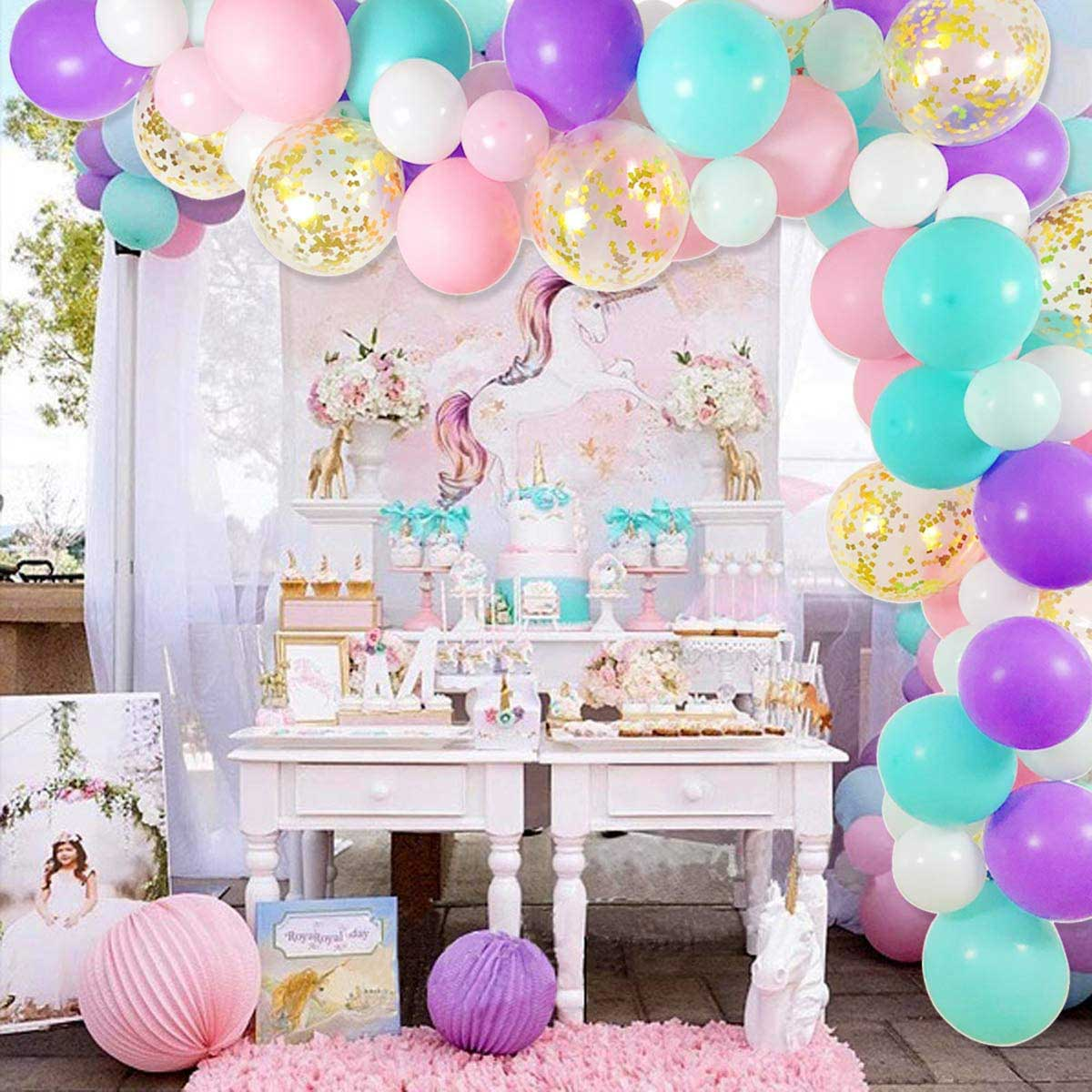 colorful balloon arch with a unicorn party table