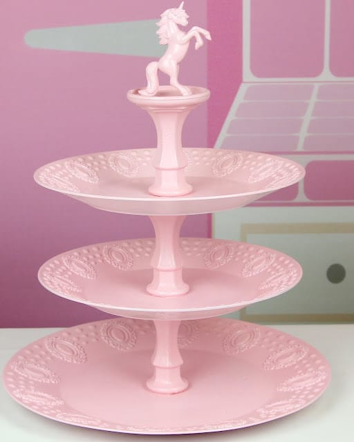 A pink cupcake stand with a unicorn on top