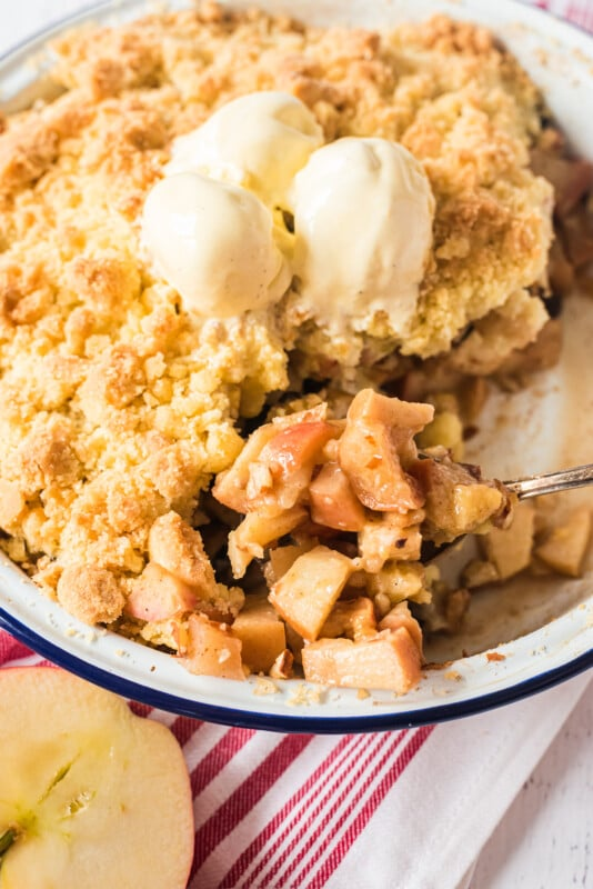 Large dish full of apple crumble topped with two scoops of ice cream