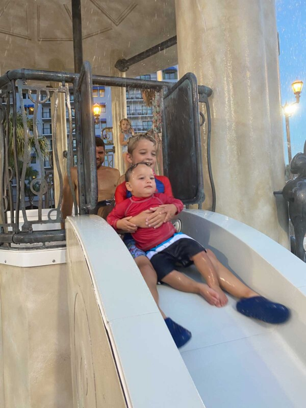 Two boys riding a water slide together