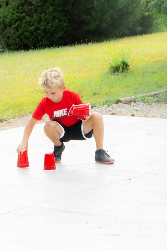 Kid placing plastic cups on a basketball court
