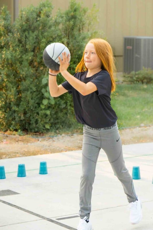 Girl holding a basketball with plastic cups on the ground