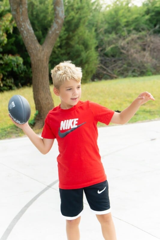 Kid in a red Nike shirt throwing a football