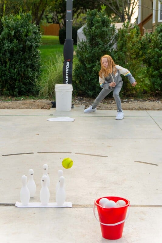 Girl bowling a baseball at bowling pins