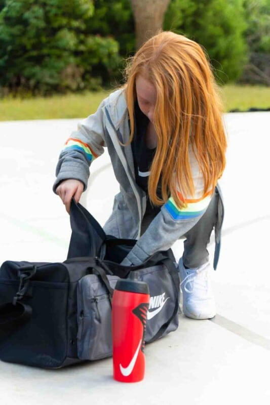 Girl grabbing sports equiptment out of a Nike bag