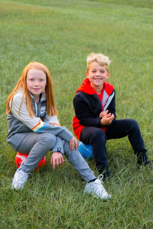 Kids sitting on soccer balls in a grassy field