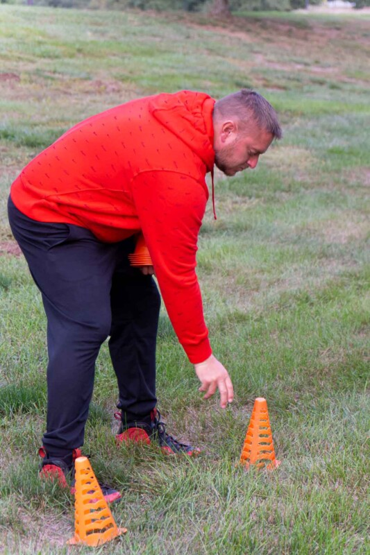 An adult setting up a cone in a grassy field