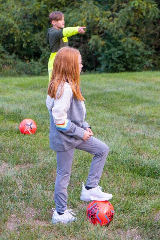 Girl with her foot on a pink soccer ball