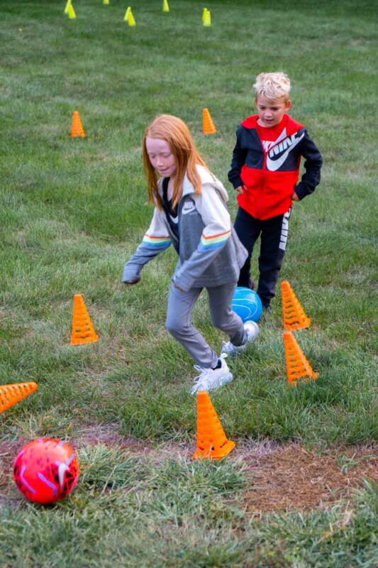 Two kids kicking soccer balls through cones