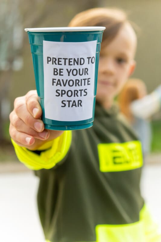 Kid holding a plastic cup that says pretend to be your favorite sports star