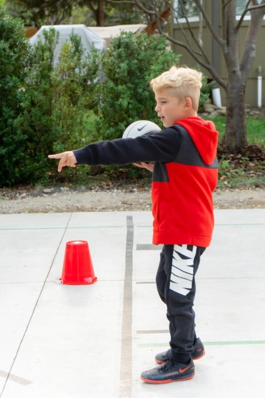 Boy holding a ball pointing at things on the ground