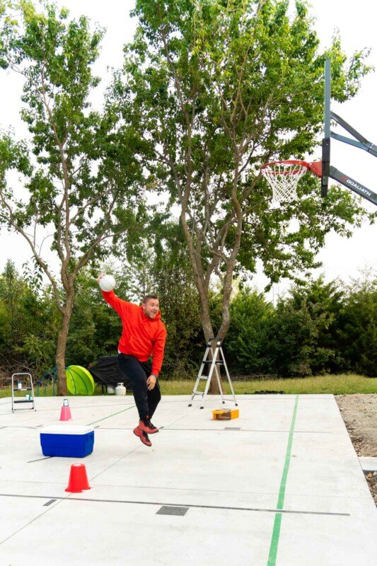 Adult in a red sweatshirt slam dunking