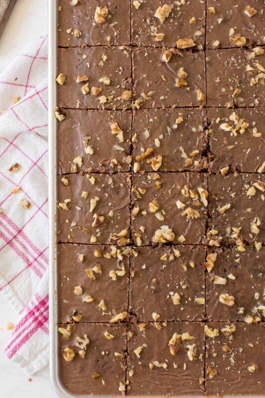 A sheet pan with cut chocolate brownie cake with walnuts