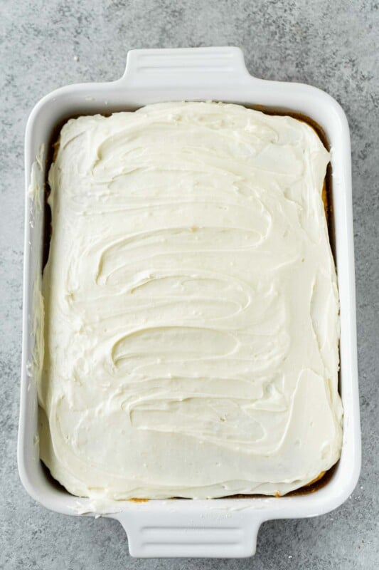 A cake with white creamy frosting in a white rectangle cake pan