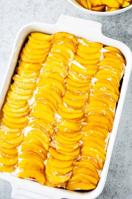 Peach cake topped with fresh peaches in a white rectangle dish