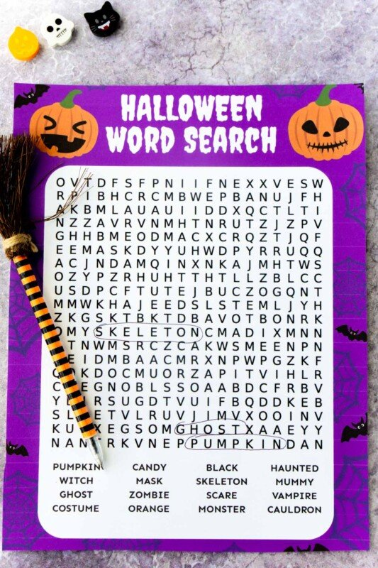 Printed out Halloween word search with a witch pen