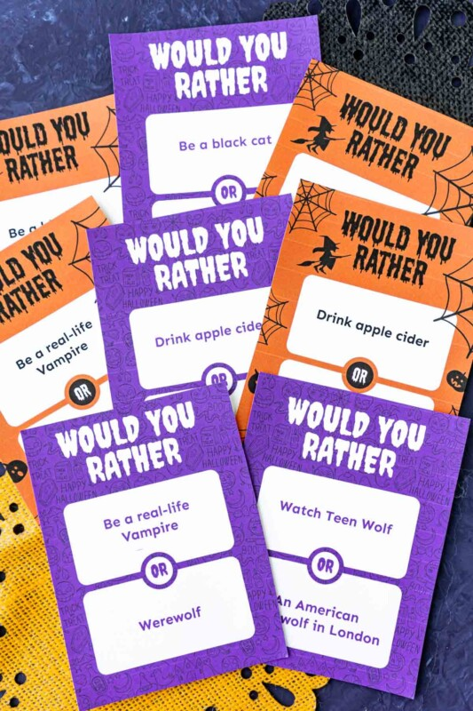Purple and orange papers with Halloween themed would you rather questions on them