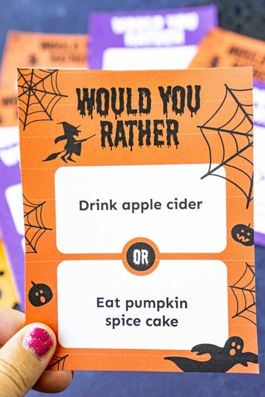 A hand holding an orange Halloween would you rather question card with witches and spiderwebs