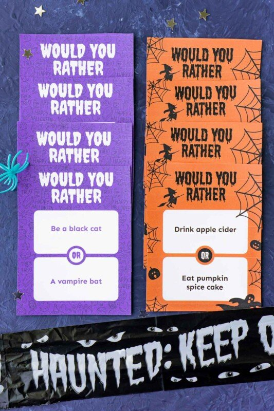 A row of purple Halloween would you rather question cards and a row of orange cards