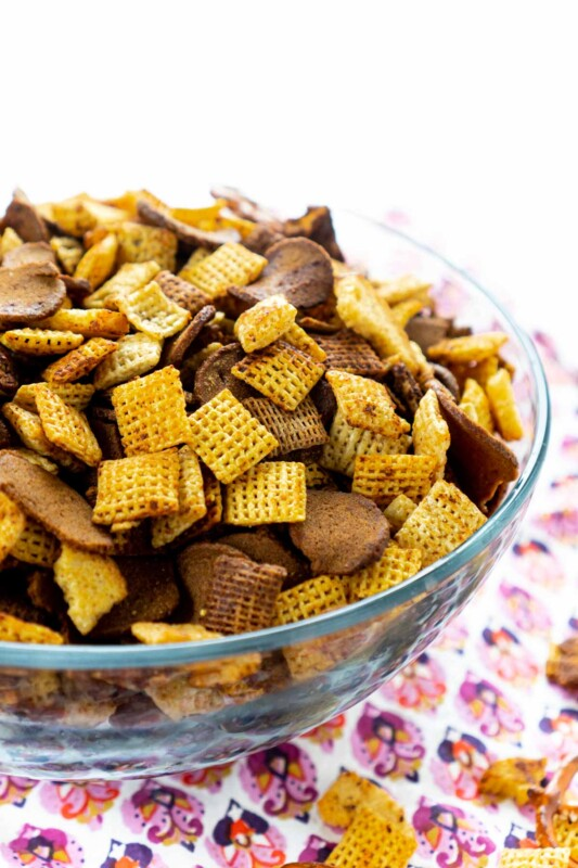 A glass bowl of homemade Chex Mix with a pink napkin underneath