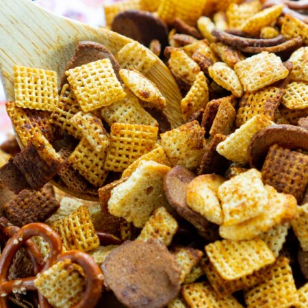 Wooden spoon in a large bowl of homemade Chex Mix