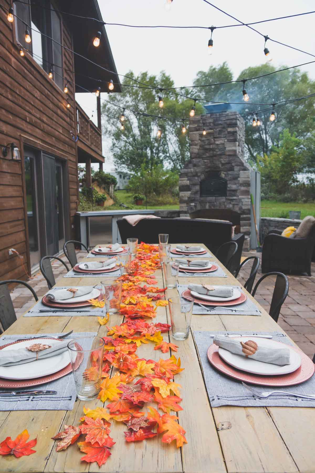A large table with fall place settings in an outdoor entertaining area